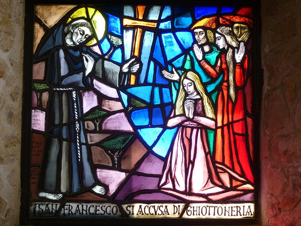 Das Glasfenster erinnert an die Zerrissenheit des Franziskus, der sich der Nascherei bezichtigt.
